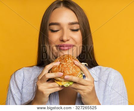 Cheat Meal. Happy Girl Eating Burger Standing Over Yellow Background. Studio Shot