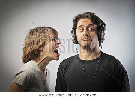 Böse Frau schreien gegen ihren Ehemann nicht zu ihr tragen Kopfhörer hören