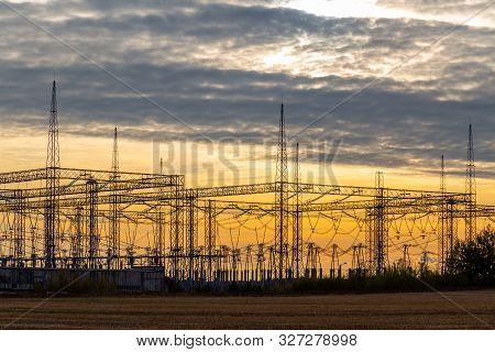 Electrical Sub Station Against Sunset Sky With Clouds. Electericity Generation And Polution.