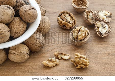 Natural Unbleached Walnuts (juglans Regia) In A White Bowl, Cracked Nuts And Kernels On A Brown Wood