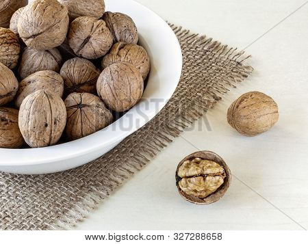 Natural Unbleached Walnuts (juglans Regia) In A White Bowl On A Rustic Style Burlap Table Napkin Ove