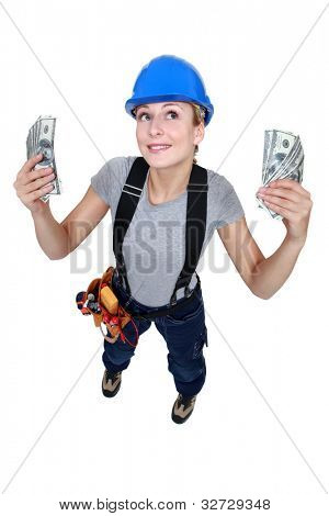 Tradeswoman holding up wads of cash