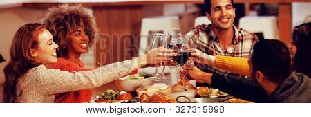 Side view of a group of young adult multi-ethnic male and female friends sitting at a table at home set for Thanksgiving dinner making a toast with glasses of red wine