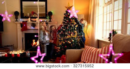 Side view of a young Caucasian woman and her young son and daughter decorating the Christmas tree together in their sitting room at Christmas time, with Christmas star decorations hanging in the