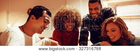 Front view close up of a group of young adult multi-ethnic male and female friends socialising sitting in the kitchen of an apartment, looking at a smartphone and laughing together