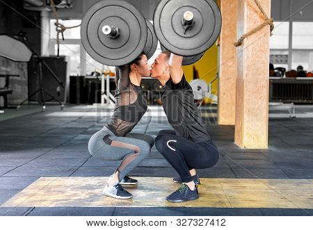 Fitness Couple Making A Barbell Jerk And Kissing Each Other. Sporty Family In Gym. Side View.
