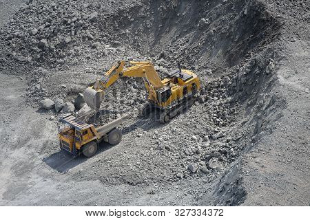 Excavator Loads Ore Into A Large Mining Dump Truck. Open Pit. Top View