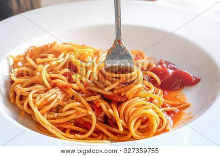 A Close Up Fork Is Wrapped In Italian Spaghetti Pasta In A White Plate With Ketchup Sauce
