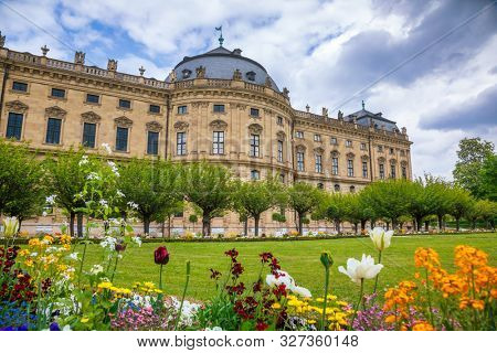 South wing of Baroque Wurzburg Residence (Wurzburger Residenz), the UNESCO World Heritage Site in Franconia, northern Bavaria, Germany, with garden flowers in foreground