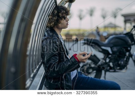 Carefree Guy Having Cigarette Near Motorbice Outdoors Stock Photo