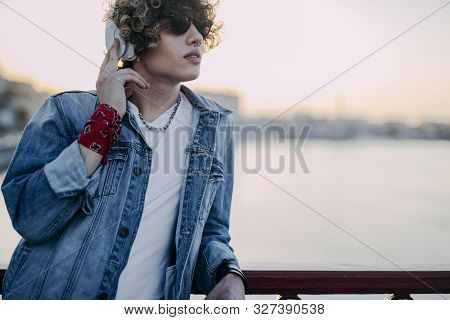 Curly Young Man In Earphones Near River Stock Photo