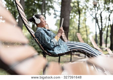 Female With Notepad Listening To Music Outdoors Stock Photo