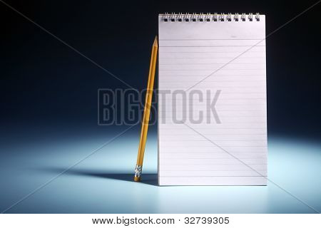 pencil resting on the plain nota pad