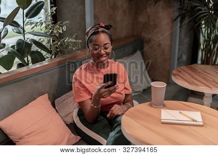 Happy Woman Using Cell Phone In Cafe Stock Photo