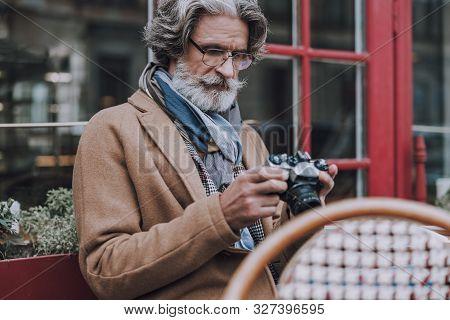 Mature Traveler Checking Photos In Camera Stock Photo