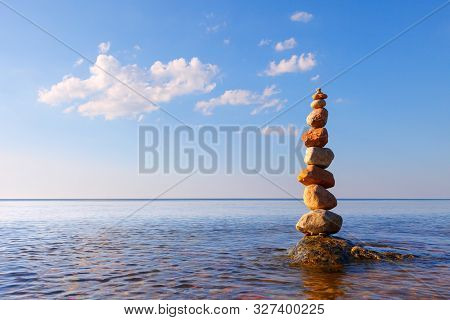 Rock Zen Pyramid Of Colorful Pebbles Standing In The Water On The Background Of The Sea. Concept Of