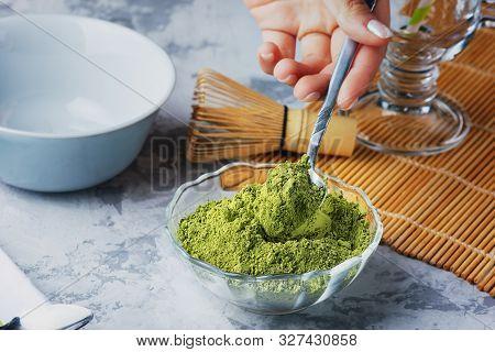 Girl Puts A Teaspoon Of Green Tea Powder In A Bowl. Matcha Green Tea Powder, Whisk And Bowl. Close-u
