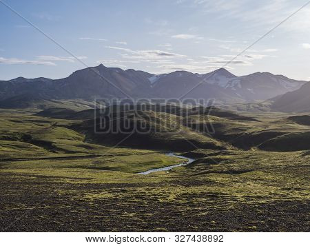 Volcanic landscape with blue river, snow covered mountains, green hills and lava gravel ground covered by lush moss. Fjallabak Nature Reserve in the Highlands of Iceland poster