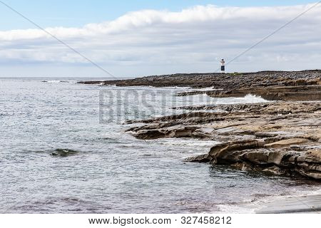 Rocks And Beach With Lighthouse In Background In Inisheer Island