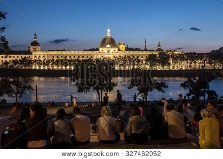 Lyon, France - July 14, 2019: French People Sitting On The Riverbank Of The Quais De Rhone, Facing H