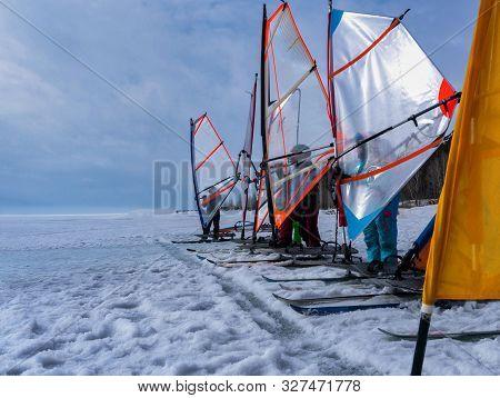 Training Team Of Children Windsurfing On The Ice Of The Frozen Sea.