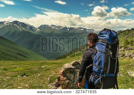 Hiker With Backpack Resting On Top Of A Mountain And Enjoying The View Of Valley.