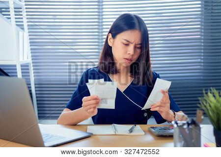 Strain Face Asian Woman Hand Holding Expense Bill And Calculation About Debt Bills Monthly At The Ta
