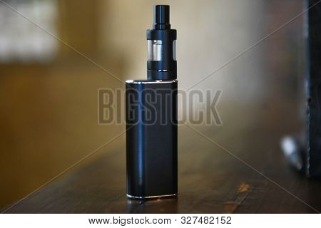 Electronic Cigarette On A Background Of Vape Shop. E-cigarette For Vaping.