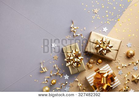 Golden Gift Or Present Boxes With Golden Bows And Confetti Top View. Christmas Background. Flat Lay