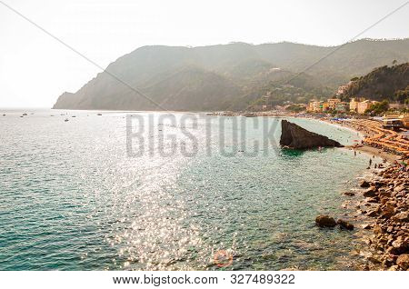 Monterosso Al Mare, Italy - September 02, 2019: Huge Rock. The Famous Beach Full Of Deckchairs, Sun
