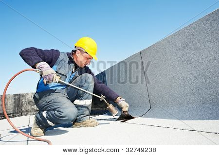 Roofer installing Roofing felt with heating and melting roll of bitumen roll by torch on flame