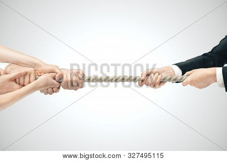 Businessman And Various Hands During Tug War On Gray Backgrounds. Business Competition Concept