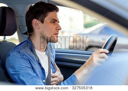 Young Brunette Man In Denim Shirt Behind Steering Wheel Of Automobile. Haggard Driver Suddenly Felt