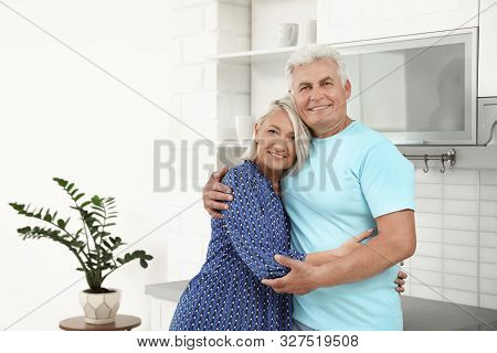 Portrait of affectionate senior couple in kitchen. Space for text poster