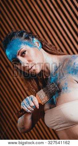 Portrait Of Beautiful Girl With Blue Facial Bodyart With Sequins. The Artist Draws Body Art On Herse