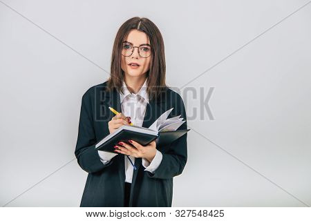 Pretty Young Businesslady In Black Suit Standing, Listening Attentively, Noting Something In Her Not