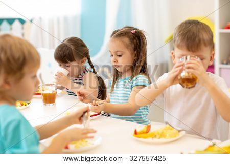 Group Of Preschool Children Have A Lunch In Day Care. Kids Eating Healthy Food In Kindergarten