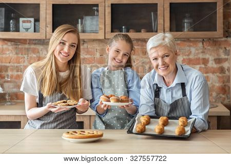 Happy Female Family Showing Freshly Baked Home Pastry, Granny, Mom And Daughter Cooking At Kitchen T