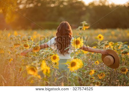 Young Asian Woman With Curly Hair In A Field Of Sunflowers At Sunset. Portrait Of A Young Beautiful
