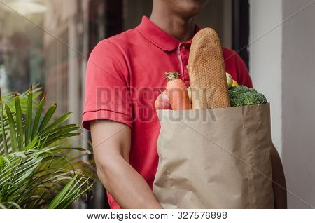 Smart Food Delivery Service Man In Red Uniform Holding Fresh Food Set Bag Waiting For Customer At Th