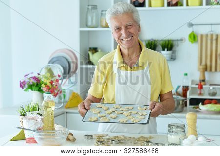 Portrait Of A Happy Elderly Man Baking Cookies