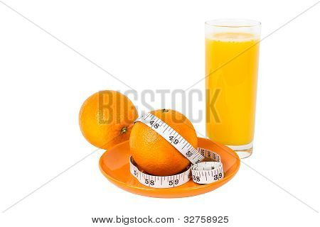Oranges With Measurement Tape On Plate With Glass Of Orange Juice