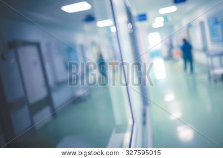 Medical Worker Walks Along The Corridor Of The Hospital During Night Watch, Unfocused Background.
