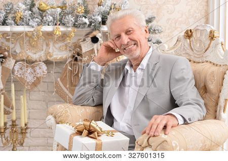 Portrait Of Senior Man With Christmas Gift