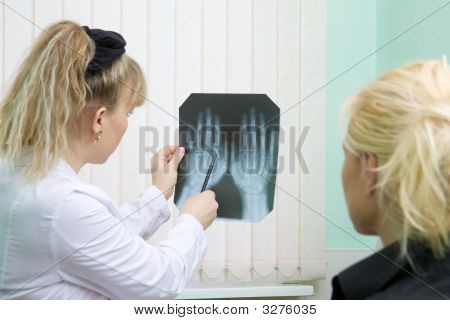 Doctor And Patient Examine X-Ray Of Hands