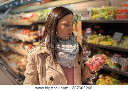 Housewives, Women With Shopping Cart In Supermarket. Gorgeous Young Woman With A Shopping Cart Looki