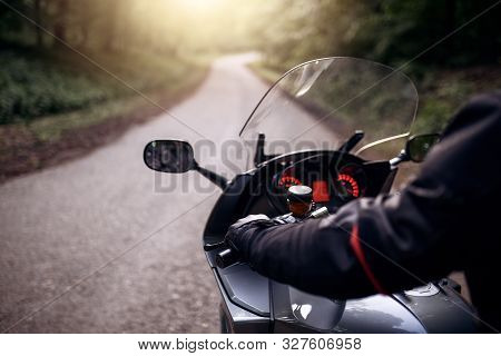 Driver Riding Motorcycle On The Road Through Forest. Biker With His Motorcycle On Street, Preparing
