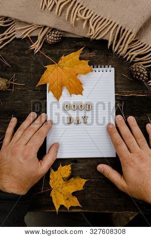 Hands And White Blank Notebook With Wooden Letters Phrase Good Day On A Dark Background With A Scarf