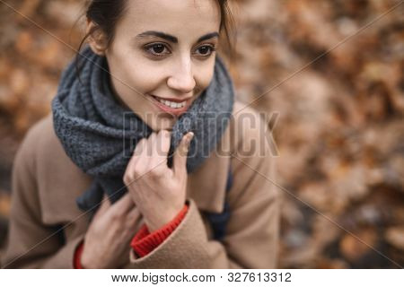 Close Up Autumn Outdoor Portrait Of Beautiful Smiling Woman In Autumn Park, Wraps In Knitted Scarf.