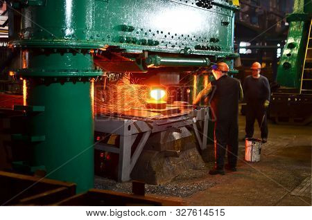 Blacksmith Processes The Red Hot Iron Under A Huge Press. Metal Forging, Stamping Under Hammer Forge
